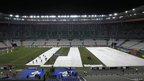 Stadium maintenance staff cover the pitch of the Stade de France stadium