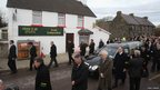 The coffin of former gaelic footballer Paidi O Se pauses at the family home