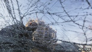 A resident is seen behind the broken windshield of vehicle after a bomb attack in Baghdad's Karrada district