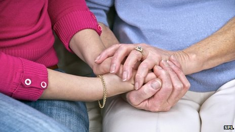 A carer and patient hold hands