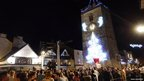 People gathered around the clock tower, lit with a Christmas tree design, in Newton Abbot in Devon, UK. Photo: James Anderson
