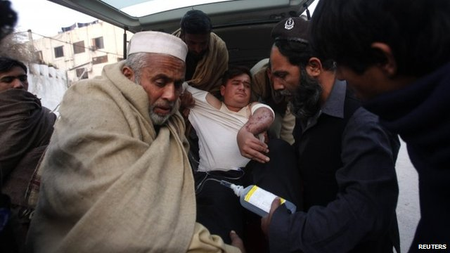An injured driver (in white) who survived a shooting by unidentified gunmen in Swabi, arrives at the Lady Reading Hospital in Peshawar January 1, 2013