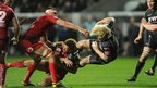 Richard Hibbard of Ospreys is tackled by Aled Thomas of Scarlets in the Boxing Day west Wales Pro12 derby at the Liberty Stadium