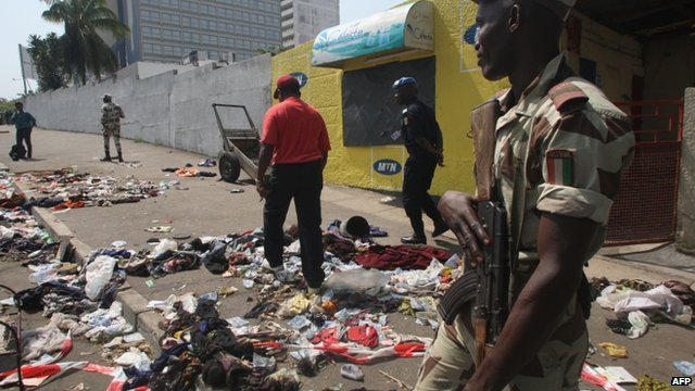 A soldier stands guard as a man walks among clothing and various items scattered on the pavement at the scene of a stampede in Abidjan, on January 1, 2013.