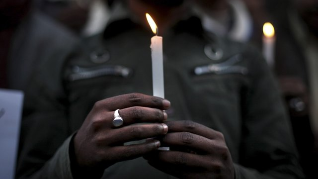 A man holds a candle in a vigil for the rape victim