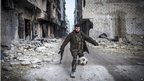 A Syrian rebel plays football in the ruined streets of Aleppo