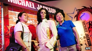 Women pose with Michael Jackson wax figure