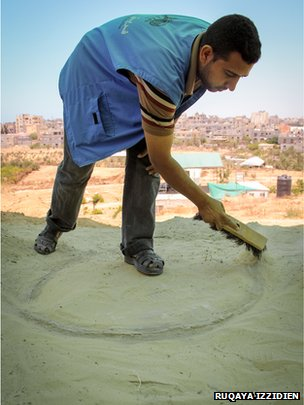 An archaeology student dusts off an ancient oven in Tel Rafah