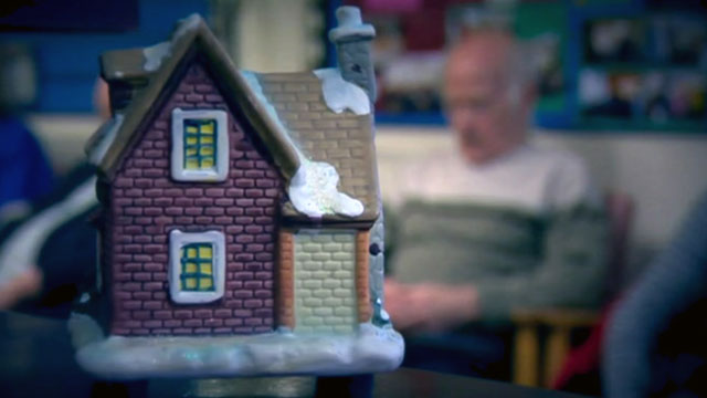 Model of snow-covered house with old man in background