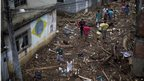 Residents walk on debris left after a flood in the Xerem neighbourhood, in Rio state.