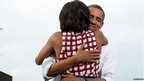 US President Barack Obama hugs First Lady Michelle Obama after she introduces him at  a campaign event in Davenport, Iowa 15 August 2012
