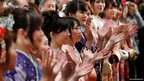 Kimono-clad workers clap their hands in a traditional New Year opening ceremony at the Tokyo Stock Exchange