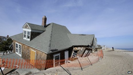 A man photographs a severely damaged beach front home in Bay Head, New Jersey, 3 January 2013