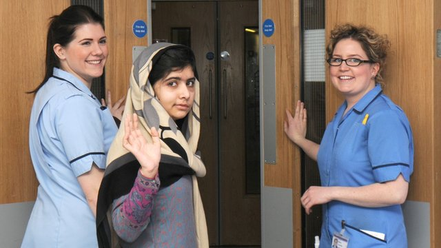 Malala accompanied by two nurses at the Queen Elizabeth Hospital in Birmingham