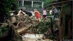 Residents of Xelem to the north of the city of Rio de Janeiro form a human chain to salvage their belongings