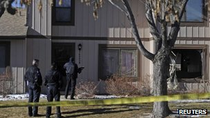 Police survey the outside of a townhouse complex following a shooting incident in Aurora, Colorado.