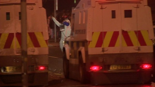 Man in hooded top and face covering throws missile at police vans