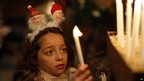 Palestinian Orthodox Christian girl lights a candle in Gaza City on 7/1/13