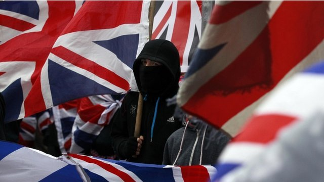 Loyalist protester surrounded by union flags in Belfast