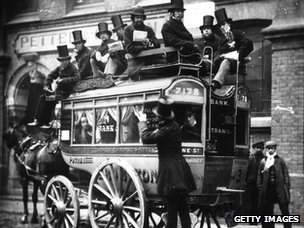 Passengers wearing top hats on a &#039;knifeboard&#039; omnibus travelling on the route between Bank and the Strand in London, in 1865