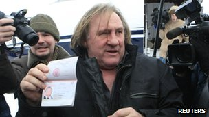 Gerard Depardieu shows his passport after arriving in Moscow