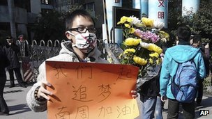"Unidentified man wearing a mask with word ""silent"" holds a banner reading: ""Let's chase our dreams together, go Southern Weekly newspaper"" during a protest outside the newspaper on 7 Jan 2013"