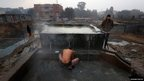 Anil Kumar Yadav takes a bath early on a chilly morning in New Delhi, India