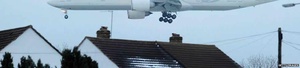Low flying plane passing over rooftops on its way to land at Heathrow