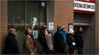 People queue to enter a government job center in Madrid, Spain.