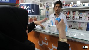 A woman buys medicine in a pharmacy in Tehran