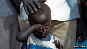 A boy who fled the conflict in Sudan's Blue Nile waits outside a clinic in Doro refugee camp, South Sudan. Photo: March 2012