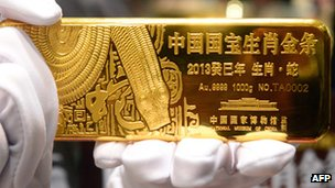 A worker holds a gold bar in a shop in China