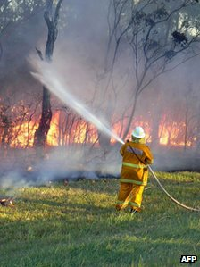 NSW Rural Fire Service worker sprays water on a bush fire at Green Point in New South Wales on 8 January 2013