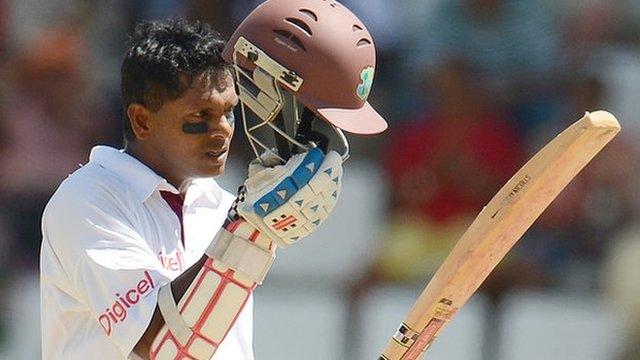 Shivnarine Chanderpaul lifts his helmet after reaching 10,000 Test runs