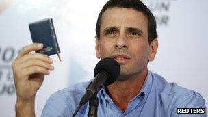 Opposition leader Henrique Capriles holds a copy of the constitution