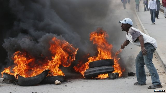 Protester with burning tyres