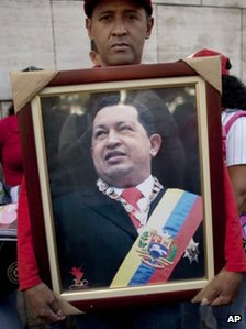 A supporter of Hugo Chavez holds a photograph of him