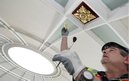 A worker fixes gold leaf to the ceiling of the Picton Reading Room