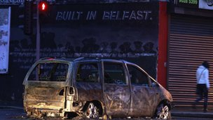 A burnt out car blocks a road in east Belfast
