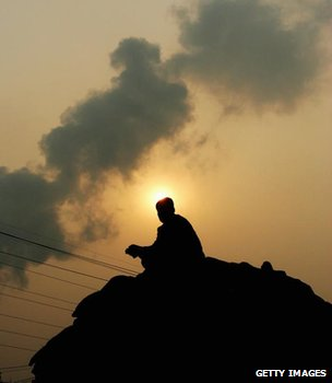 Man sitting on coal sacks at a Chinese power station (Getty Images)