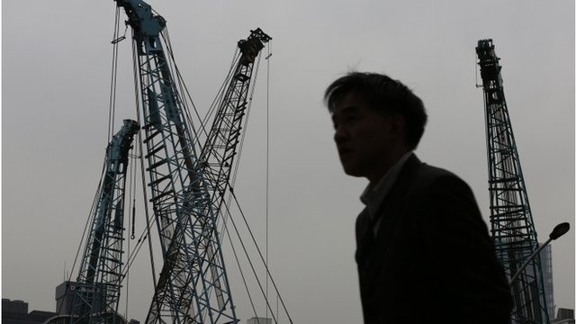 Worker in front of construction cranes