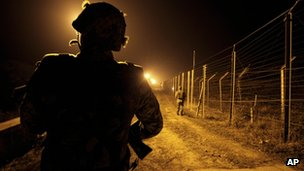 An Indian Border Security Force (BSF) soldier stands guard during a night patrol near international border fencing at Suchet Garh in Ranbir Singh Pura, Thursday, 10 Jan 2013