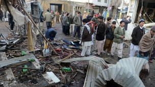 Local residents gather at the site of the overnight twin suicide bombings in Quetta