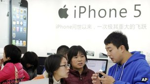 A member of staff talks to customers at an Apple store in China