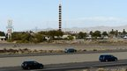 Traffic moves on US Route 15 as it passes the world's tallest thermometer in Baker, California