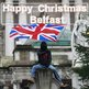 Masked protester waves union flag in front of Belfast City Hal Happy Christmas sign