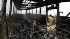 Men walk past the burned remains of a commuter bus in Majidun, an area in Lagos, Nigeria, on 7 January 2013.