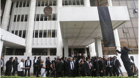 Sri Lankan lawyers hang a black flag as a sign of protest against the government's impeachment bid outside the Colombo court complex