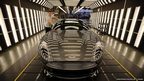 An Aston Martin Vanquish is inspected by hand inside a light booth by technician Matthew Goss  in Gaydon, England