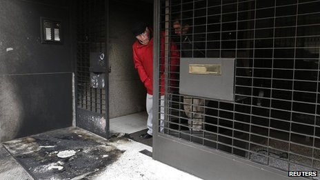A resident stands at the burned entrance of a building following a series of arson attacks against journalists in Athens, 11 January 2013